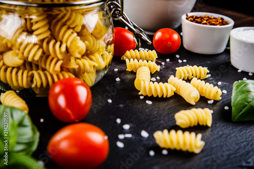 Raw pasta with spices on black stone on wooden background - 214230597