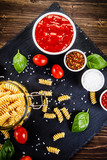 Raw pasta with spices on black stone on wooden background - 214230743