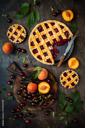 Fotobehang Kersen Homemade cherry pie on rustic background with cherries and peaches