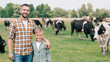 happy father and son smiling at camera while standing near grazing cattle at farm