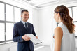 real estate business, sale and people concept - male realtor with clipboard showing contract document to customer at new office room