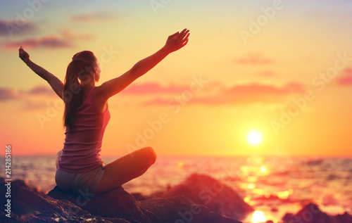 Leinwandbild Motiv Relaxation And Yoga At Sunset - Girl With Open Arms Looking Ocean