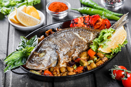 Baked dorado fish with vegetables and lemon on pan on wooden background close up. Delicious dish of seafood © Jukov studio