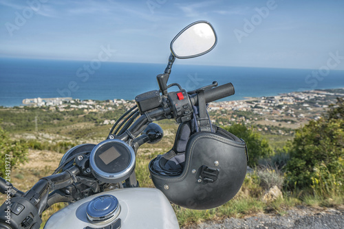 Motorcycle standing on a top mountain, near a coastline