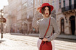 Outdoor portrait of young beautiful fashionable woman wearing stylish red hat, striped turtleneck, white jeans, holding red bag. Copy, empty space for text