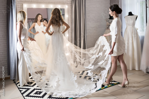 Wedding consultant helps bride choosen wedding dress in salon. Mother and daughter in wedding shop