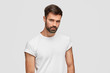 Portrait of serious bearded male hipster looks confidently at camera, has dark hair, wears casual t shirt, hears attentively something important, stands against white wall, has strong body shape