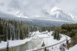 Empty Curving Railway Track on the Riverbank in a Beautiful Snowy Mountain Landscape on a Winter Day. Banff National Park, AB, Canada.