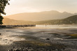 Majestic Sunset over a Bay at Low Tide with a Pier Crowded with People. Port Moody, BC, Canada.