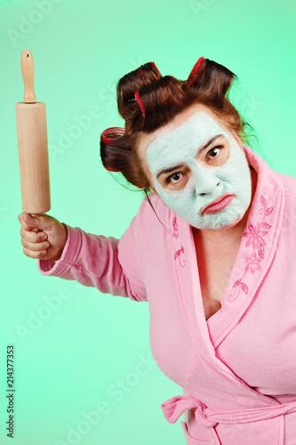 femme ronde et drôle avec bigoudis fâchée avec rouleau à pâtisserie