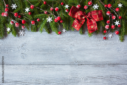 Christmas wooden background with spruce branches, red berries and bow