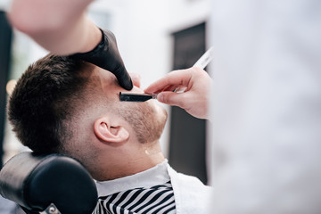 Shave beards in barbercos. Men's haircut and facial care. Barber makes a haircut to the client.