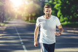 Waist up portrait of serious male running in park. He is listening to music with concentration while jogging. Copy space in left side