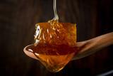 Honey Flows Over Comb in Wooden Spoon - 214400367