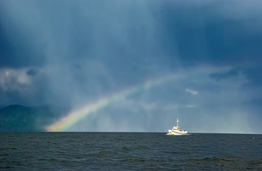 boat sailing along a mountain lake against the background of rain and rainbow © Lyubov Furs