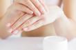 Leinwandbild Motiv Groomed woman's hand applying moisturizing cream on her hand. Jar of herbal cream. Care about clean, soft and smooth body skin.