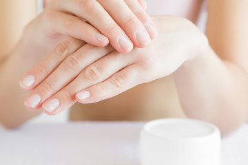 Groomed woman's hand applying moisturizing cream on her hand. Jar of herbal cream. Care about clean, soft and smooth body skin.