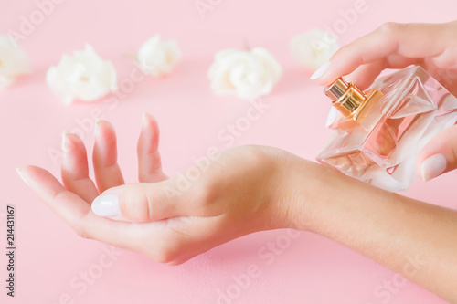Leinwandbild Motiv Young, perfect, groomed woman's hands holding a perfume bottle. Care about fresh fragrance of body. Beautiful, white roses on pastel pink table. Fresh flowers.