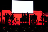 Silhouette of an people  on the stage in the front of a colorful background. - 214431966