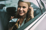 Businesswoman making phone call in cab - 214438140