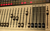 music, technology, people and equipment concept - hands using mixing console in sound recording studio - 214448561