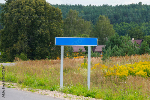 Canvas Betoverde Bos An empty road sign on the background of houses surrounded by trees