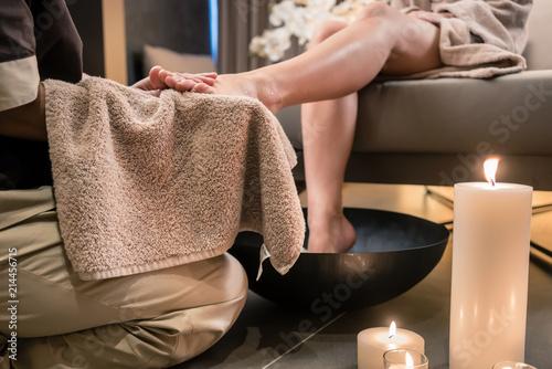 Azjatycki terapeuta wyciera stopy kobiecego klienta miękkim ręcznikiem po terapeutycznym praniu w centrum odnowy biologicznej
