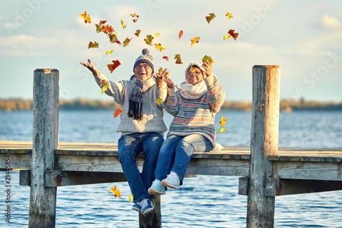 Leinwandbild Motiv lachendes Seniorenpaar im Herbst
