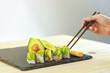 japanese avocado sushi on black slate stone and wood table
