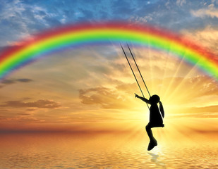Silhouette, little girl child on a swing rainbow over the sea. © Prazis Images