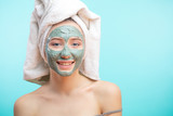 Young woman wearing towel on head applying facial clay Mask. Beauty Treatments. Close-up portrait of beautiful caucasian girl isolated over blue background. Facial Treatment. High Resolution.