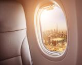Airplane interior with window view of Dubai city