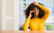 Quadro African american woman using smartphone stressed with hand on head, shocked with shame and surprise face, angry and frustrated. Fear and upset for mistake.