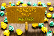 Text sign showing Moments That Matter. Conceptual photo Meaningful positive happy memorable important times Paperclip grip cardboard with texts many colorful lobs scattered on wooden desk.