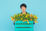 Happy middle-aged woman with glasses holding box of tulips in blue background - 214504558