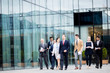 Young confident businesspeople in suits moving along modern glass building