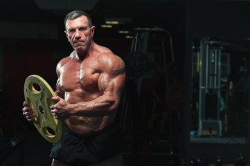 Portrait of high level bodybuilder posing with heavy weights in hands. Strong mature man with relief body © pavel_shishkin