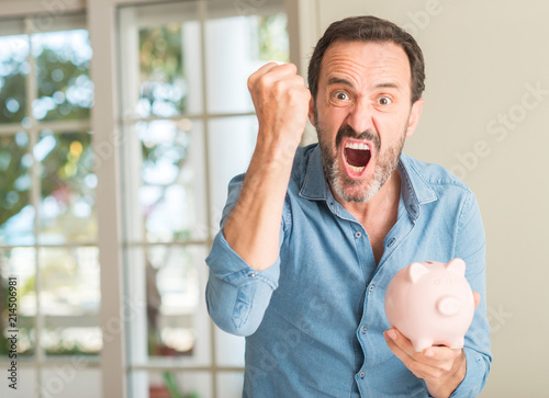 Leinwandbild Motiv Middle age man save money on piggy bank annoyed and frustrated shouting with anger, crazy and yelling with raised hand, anger concept