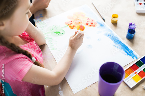 Foto Murales Little girl sitting at the table painting and using watercolor paints