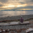 Man sitting on log looking at beautiful sunrise Miracle Beach in the Comox Valley, British Columbia, Canada.  Square crop.