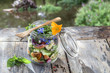 Leinwanddruck Bild - Vegan salad in a jar: vegetables,and flowers,pasta, smoked salmon, for a healthy homemade raw food concept. river background