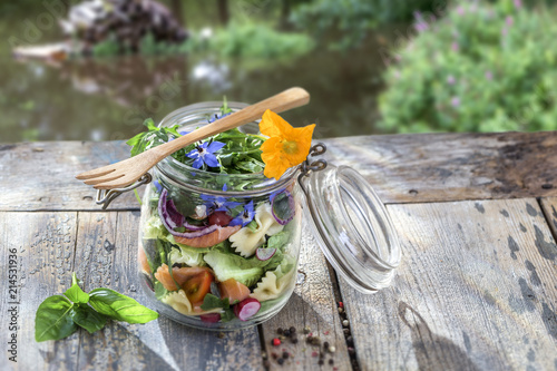 Leinwanddruck Bild Vegan salad in a jar: vegetables,and flowers,pasta, smoked salmon, for a healthy homemade raw food concept. river background