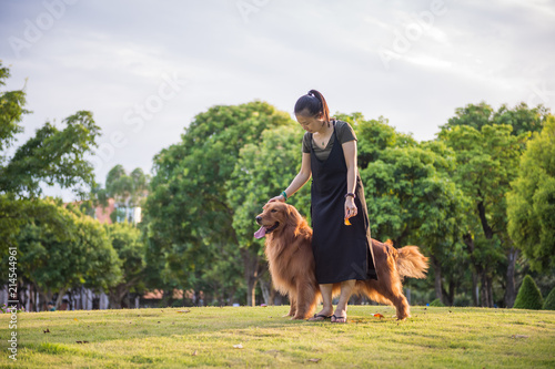 Foto Murales Golden retriever and girls playing in the park