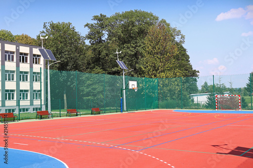 Lubno, Poland - july 9 2018:Basketball shield in an open stadium in the courtyard of a rural school. Sports ground for football with artificial multicolored coating. Lighting on natural sources