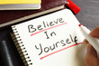 Man is writing Believe In Yourself in a note. Motivation.