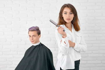 Confident young female hairdresser looking at camera standing in front of client. Hairstylist keeping black plastic comb, sharp metallic scissors, wearing white shirt. Client with toned lilac hair. © serhiibobyk