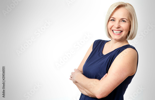 Leinwandbild Motiv Attractive middle aged woman with folded arms on white background