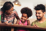 Mom and dad drawing with their daughter. African american family spending time together at home. - 214567943