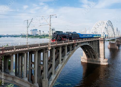 Steam locomotive with passenger train in motion on bridge