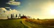 Leinwandbild Motiv typical Tuscany countryside landscape; sunset over rolling hills and Tuscany village